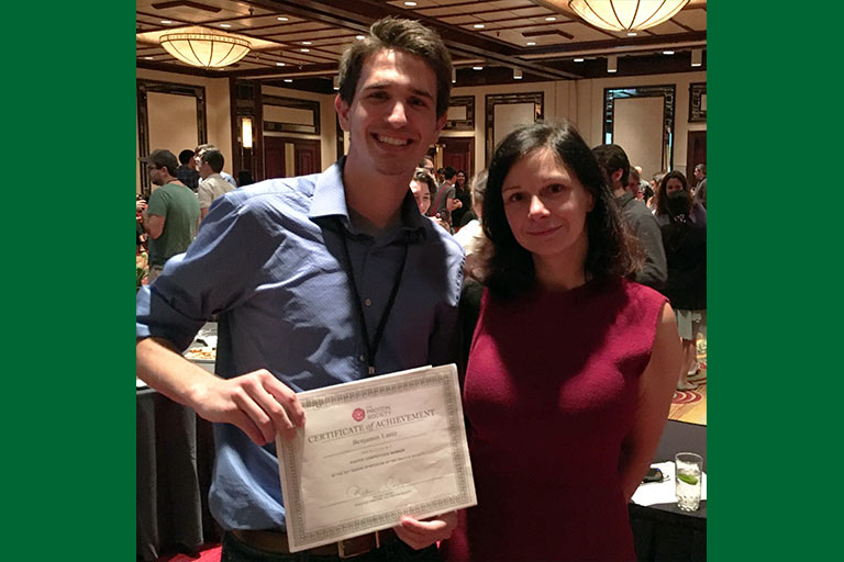 "Benjamin Lantz holding his ""Top Undergraduate Poster Presenter Award"" at the Protein Society's 31st Annual Symposium in Montreal, Canada, with Raluca Cadar, executive director."