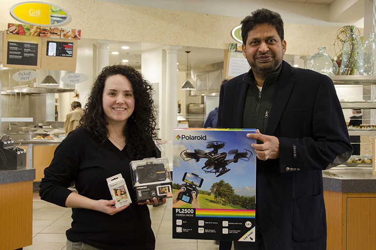Hannah Spearman, unit marketing coordinator for Sodexo at ENMU, with Dr. Ajay Singh and his Polaroid prize package.